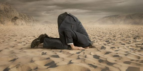 Person wearing suit on knees with head buried in the sand